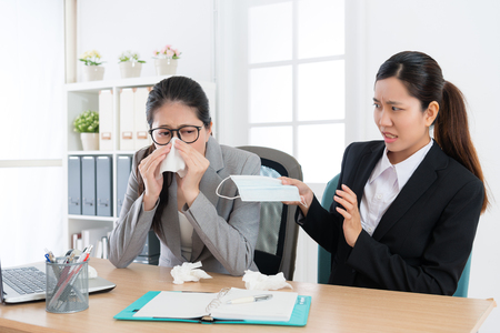 female office worker catches cold using tissue blowing nose during conference time and colleague feeling afraid giving medical mask for her preventing infection.