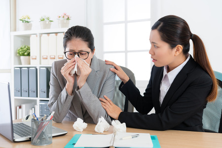 beautiful young office worker girl worried company leader woman who catching cold and having allergy problem feeling painful blowing nose.
