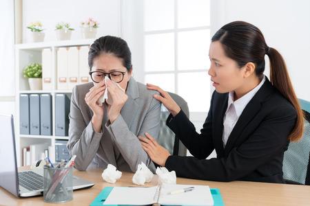 piękna młoda dziewczyna pracownik biurowy martwiła się liderką firmy, która łapie przeziębienie i ma problem z alergią, czując bolesne dmuchanie w nos.