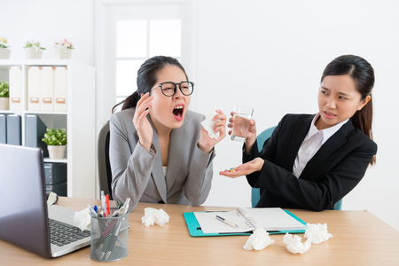 business woman sneezing while her worker partner looking at her feeling fear in office and giving pills with water.