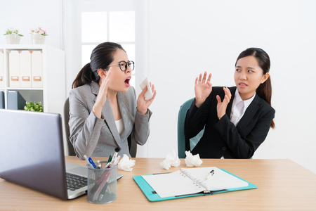 attractive female company manager sneezing and woman co-worker looking at her feeling afraid when they having meeting in office. Banque d'images