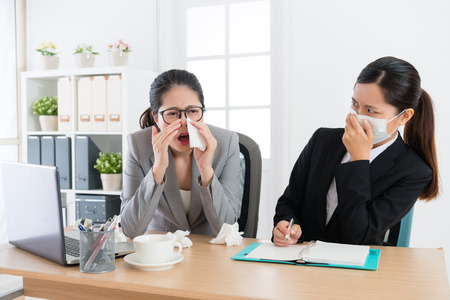 office worker woman sneezing during conference time and her colleague feeling afraid keeping away.