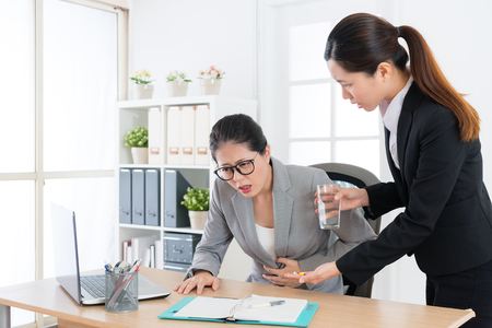 beauty attractive woman leader getting gastroenteritis illness feeling painful and young pretty female assistant giving her treatment pill. Stockfoto