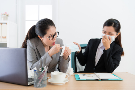 attractive beauty girl company employee having disease problem coughing and female co-worker provide medical mask for her in order to avoid infection. Standard-Bild
