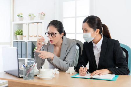 young elegant company manager woman having nose allergy problem and office worker partner wearing medical mask meeting with her. Foto de archivo