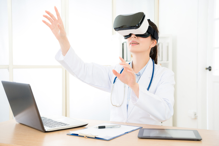attractive pretty doctor wearing VR technology device looking at online medical 3D video and using hands organizing content. Stok Fotoğraf