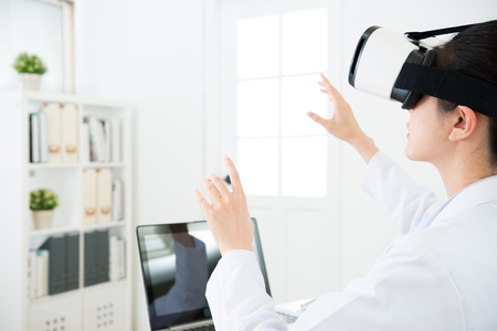 beauty young female doctor wearing VR technology goggles looking 3D video and using hands organized report document on simulation screen.