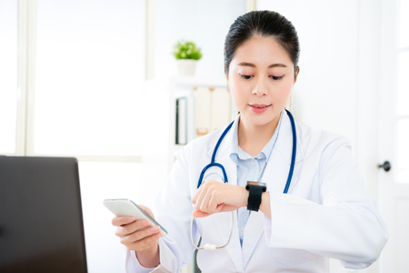 Smiling pretty doctor woman looking at smartwatch confirm already connection with mobile cell phone when she working in office using mobile laptop online service.