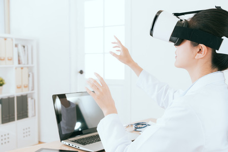 professional young female doctor wearing virtual reality goggles device working and using hands established medical report through 3D video. Stok Fotoğraf