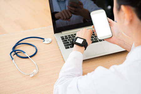 selective focus photo of online service doctor working in office and using mobile cell phone connecting smartwatch with white blank screen.