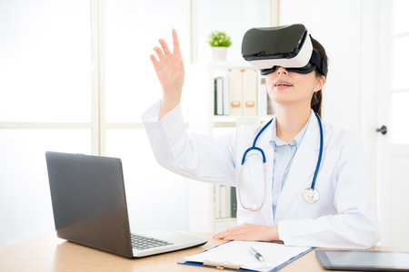 happy young doctor woman wearing virtual reality goggles device experienced 3D video technology and using hand touching simulation screen.