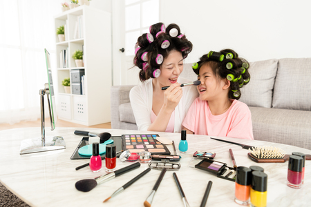 mother with daughter using cosmetics makeup together at home.