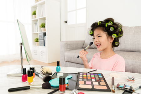 happy lovely little girl children looking at mirror and using cosmetic brush makeup by herself in living room.