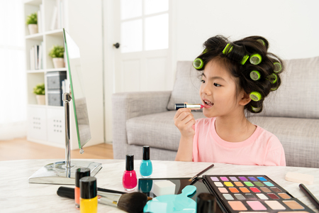 cute beautiful little girl kid using lipstick makeup.