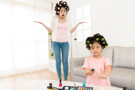 shocked pretty mother feeling angry and incredibly when she finding little girl using nail polish to paint finger by herself. Stock Photo