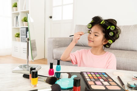 smiling pretty female kid using brush looking at mirror when she painting eyeshadow with many colorful cosmetics powder. Stock Photo - 93135367