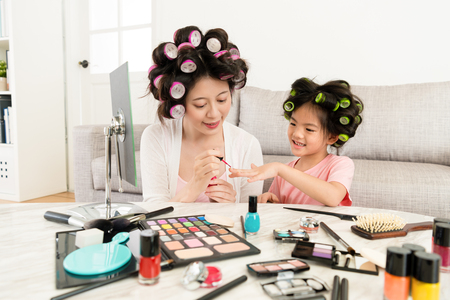 elegant young mom using pink color nail polish helping cute little daughter dress up when they makeup with many cosmetics at home.