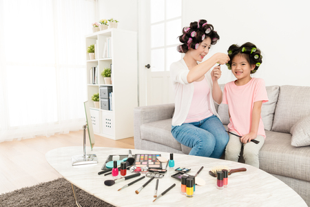 happy smiling little girl children sitting on sofa couch looking at camera when young pretty mother using hair curler helping her dress up.