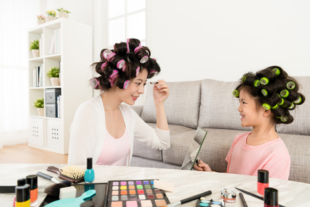 smiling happy little girl kid holding mirror when young beautiful woman using cosmetics brush makeup and using colorful powder painting eyeshadow.
