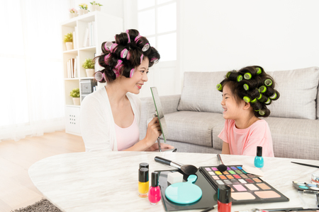 happy mother holding mirror for smiling cute little daughter looking beauty face when they finished makeup in living room.