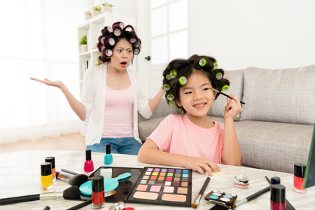 happy young girl children looking at mirror using cosmetics brush painting eyeshadow and her mother in back feeling dumbfounded.