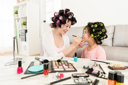 smiling beautiful woman helping little girl makeup and using cosmetic brush to paint lipstick.