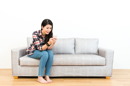 smiling young woman sitting on wooden floor sofa couch relaxing and using mobile cell phone chatting with friend in white background. Banco de Imagens