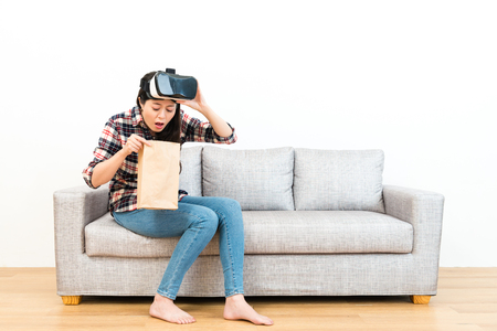 young pretty woman using VR device experiencing 3D game getting dizziness and sitting on wooden floor sofa couch vomiting in white background.
