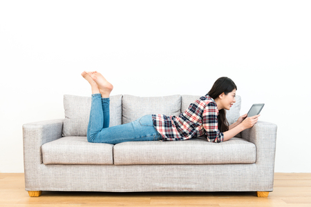 elegant young woman on wooden floor sofa couch using mobile digital tablet in white background.
