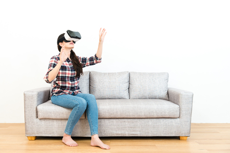 Attractive smiling girl using hands catching simulation screen in white background when she sitting on sofa experiencing VR device goggles.