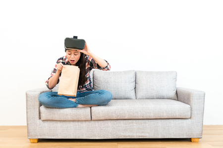 painful sick woman sitting on sofa couch vomiting because she using virtual reality goggles watching 3D video feeling uncomfortable.