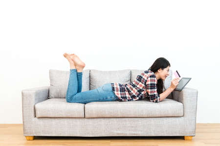 happy beautiful girl on wooden floor sofa looking at mobile digital tablet pad browsing online shopping websites and using personal credit card e-commerce paying.