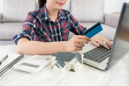 Attractive beauty housewife holding credit card in living room and using online e-commerce payment system paying house tax.