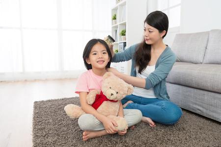 young elegant woman using brush helping smiling pretty girl children combing hair. 免版税图像