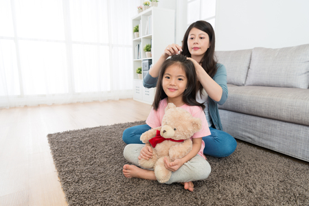 young pretty little daughter looking at camera smiling and holding teddy bear toy sitting on floor when mother tied her hair.