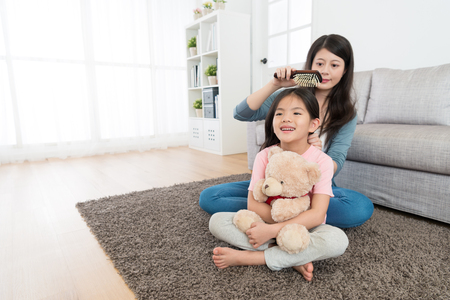 A happy cute girl holding a teddy bear sitting on the living room floor with her pretty young mother combing her hair in the morning.