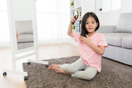cute pretty little girl sitting on living room floor looking at camera and using brush combing hair in morning when she wake up. Reklamní fotografie