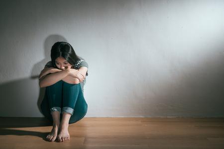 恐怖感を感じ、白い壁の背景でリラックス木製の床に座って経験を乱用した美しい若い女性。