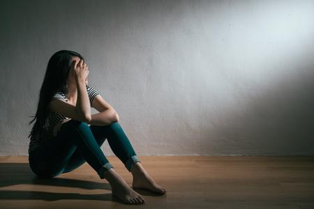 la ragazza attraente di bellezza si rompe con la tristezza di sensibilità del ragazzo che si siede sul pavimento di legno che fantastica e che grida nella priorità bassa bianca. Archivio Fotografico
