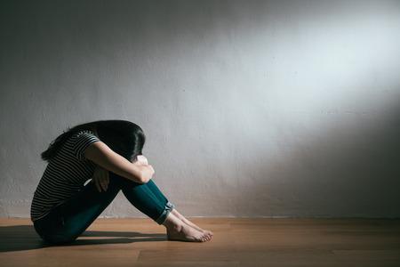 tristesse jeune femme se reposer dans un fond blanc quand elle aime fatigué et assis sur un plancher en bois se cachant doucement à la réception Banque d'images