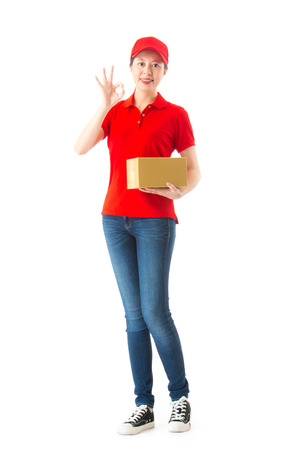 confident beauty girl delivery worker looking at camera showing ok gesture and holding small box standing in white background. full length photo. Stock Photo