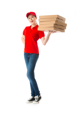 happy beautiful female pizza delivery worker standing in white background with many box and looking at camera.
