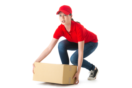 young beautiful woman delivery company employee squat down to hold big heavy box package feeling difficulty isolated on white background.