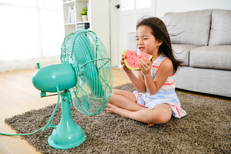 attractive young female little children sitting in front of electric fan blowing cooling wind and eating cold watermelon feeling refreshing during summer season.