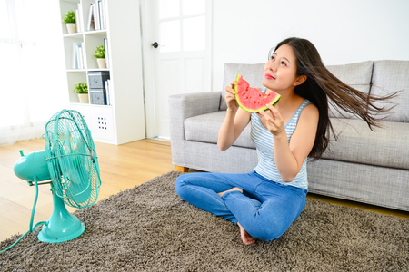 smiling pretty woman blowing electric fan and eating watermelon in summer season.