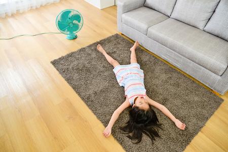 Foto di vista dell'angolo alto della bambina attraente adorabile che si riposa sul tappeto che dorme riposando e soffiando ventilatore elettrico che gode del vento fresco durante la stagione estiva. Archivio Fotografico