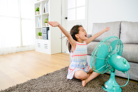 young pretty girl children sitting on living room floor blowing electric fan during summer day and opening arms enjoying cool wind to refreshing.