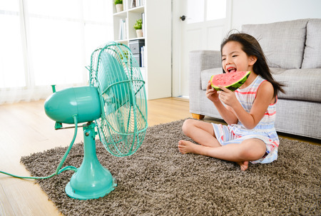 happy pretty little girl children sitting on floor enjoying cooling wind from electric fan and eating fresh watermelon during summer season. 版權商用圖片
