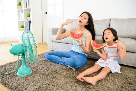 jeune maman avec une mignonne petite fille se sentant chaude en été assis sur le plancher du salon soufflant un ventilateur électrique rafraîchissant et mangeant une pastèque froide. Banque d'images
