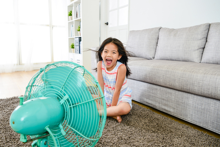 happy attractive female kid blowing cooling wind from electric fan feeling cold looking at camera laughing in summer time. Stock Photo